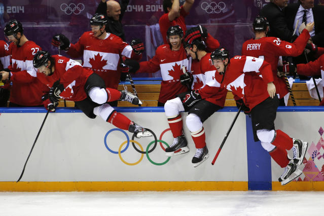 The Canadian bench jumps out of the bench area to celebrate their 3-0 win over Sweden in the men's gold medal ice hockey game at the 2014 Winter Olympics, Sunday, Feb. 23, 2014, in Sochi, Russia. (AP Photo/Petr David Josek)
