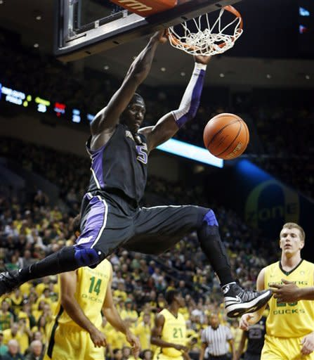 Washington's Aziz N'Diaye, top, slams a dunk over Oregon's Arsalan Kazemi (14) and E.J. Singler, right, during the first half of an NCAA college basketball game in Eugene, Ore., Saturday, Jan 26, 2013. (AP Photo/Chris Pietsch)