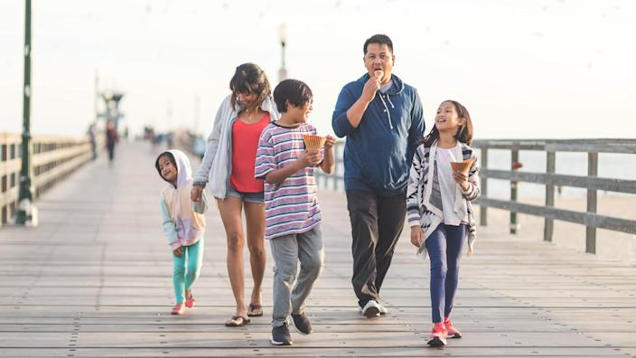 Two Filipino parents and their three children enjoy huge waffle ice cream cones on a California boardwalk by the beach.
