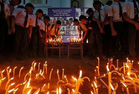 FILE PHOTO: Students light candles during a vigil at a prayer meeting to show solidarity with the victims of Sri Lanka's serial bomb blasts, outside a church in Kolkata, India, April 23, 2019. REUTERS/Rupak De Chowdhuri