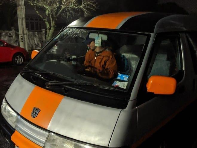 An orange and gray van at night in New Zealand