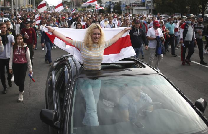 A woman standing in a car, waves an old Belarusian national flag, during a Belarusian opposition supporters' rally protesting the official presidential election results in Minsk, Belarus, Sunday, Sept. 13, 2020. Protests calling for the Belarusian president's resignation have broken out daily since the Aug. 9 presidential election that officials say handed him a sixth term in office. (Tut.by via AP)