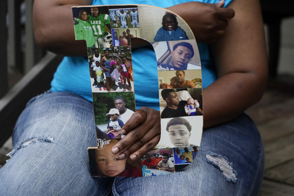 """Tammie Townsend holds a collage of photographs of her eldest son, Willie Jones Jr., 21, with family members, as she speaks about the incident where he was found hanging from a tree in his girlfriend's Scott County yard three years ago, April 27, 2021 at his grandmother's home in Forest, Miss. The collage are in the form of a """"D,"""" which played off his nickname, """"Duke."""" A Hinds County judge recently awarded the family $11 million in a civil suit related to his death. (AP Photo/Rogelio V. Solis)"""