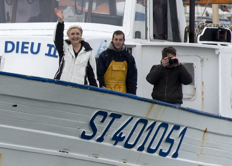 """French far-right leader and candidate for the presidential election Marine le Pen, left, waves from a fishing trawler as she arrives from a sea trip in Grau-du-Roi, southern France, Thursday April 27, 2017. After """"the battle of Whirlpool,"""" when Marine Le Pen and centrist candidate Emmanuel Macron both went hunting for France's blue-collar vote, the presidential candidates clashed over fish in a return to more traditional campaigning. (AP Photo/Jean-Paul Bonincontro)"""