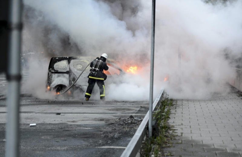 Firemen extinguish a burning car in the Stockholm suburb of Rinkeby after youths rioted in several different suburbs around Stockholm for a fourth consecutive night, late May 23, 2013. Youths in immigrant-heavy Stockholm suburbs torched cars and threw rocks at police in riots believed to be linked to a deadly police shooting of a local resident in the suburb of Husby.  (AP Photo/Scanpix, Fredrik Sandberg)   SWEDEN OUT
