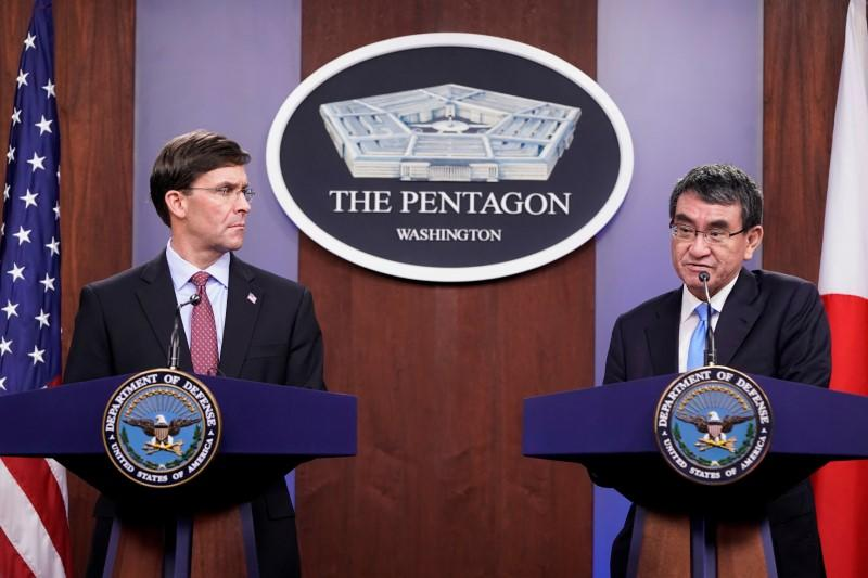 U.S. Secretary of Defense Mark Esper looks on as Japan's Defense Minister Taro Kono speaks during a joint news conference at the Pentagon in Washington