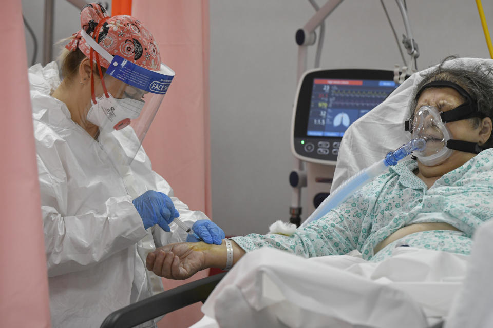 A woman breathing through an oxygen mask gets an injection in the emergency room, turned into a CODIV-19 unit due to the high number of cases, at the Bagdasar-Arseni hospital in Bucharest, Romania, Tuesday, Oct. 12, 2021. Romania reported on Tuesday nearly 17,000 new COVID-19 infections and 442 deaths, the highest number of coronavirus infections and deaths in a day since the pandemic started, as the nation's health care system struggles to cope with an acute surge of new cases.(AP Photo/Andreea Alexandru)
