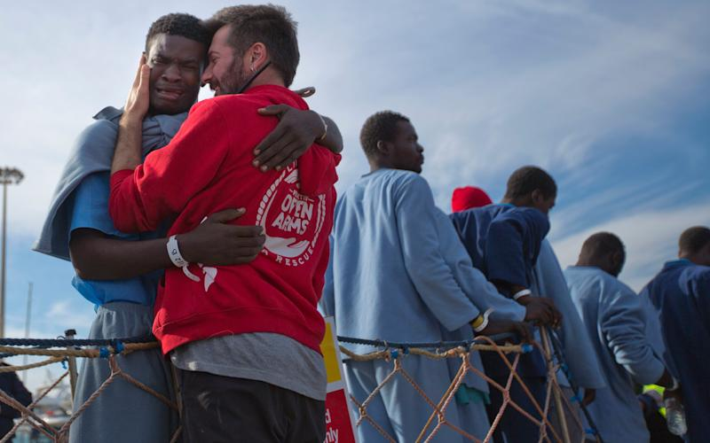 A migrant from Cameroon cries with an NGO rescue worker after being rescued last month. Italian authorities have reported a fresh wave of migrant rescues to Sicily in March - Emilio Morenatti