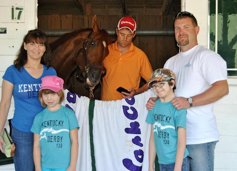 In this May 5, 2012 photo provided by the Hudson family, Hope Hudson, 12, from Missouri,  in plaid hat, and her family Hope's mother, Jennifer; sister, Alaina, 8; and father, Nathan Hudson, pose with Kentucky Derby winner I'll Have Another, in Louisville, Ky. The worker in orange is unidentified. Hope, who is battling a rare disease, was getting her first up-close look at the sleek thoroughbreds she loves, thanks to the Make-A-Wish Foundation. There will be a reunion at the Preakness this month for the frail girl and a trainer who met just before the trainer's horse gained fame as winner of this year's Kentucky Derby (AP Photo/Hudson family)