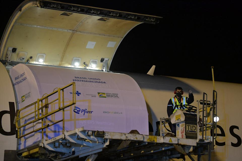 Workers download a container with 1,000,000 doses of the Pfizer-BioNTech vaccine against COVID-19 from an aircraft upon its landing at the Viracopos International Airport in Campinas, some 100 km from Sao Paulo, Brazil on April 29, 2021. - Brazil received Thursday a first lot of 1,000,000 doses of the Pfizer-BioNTech vaccine developed by US drugmaker Pfizer and BioNTech of Germany. (Photo by NELSON ALMEIDA / AFP) (Photo by NELSON ALMEIDA/AFP via Getty Images)