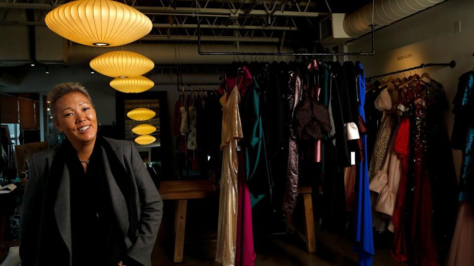 Stylist Jeanne Yang stands next to a rack of clothes.