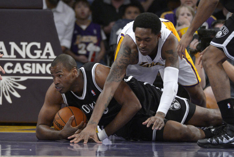 Brooklyn Nets center Jason Collins, left, battles for a loose ball with Los Angeles Lakers guard MarShon Brooks during the first half of an NBA basketball game, Sunday, Feb. 23, 2014, in Los Angeles. (AP Photo/Mark J. Terrill)