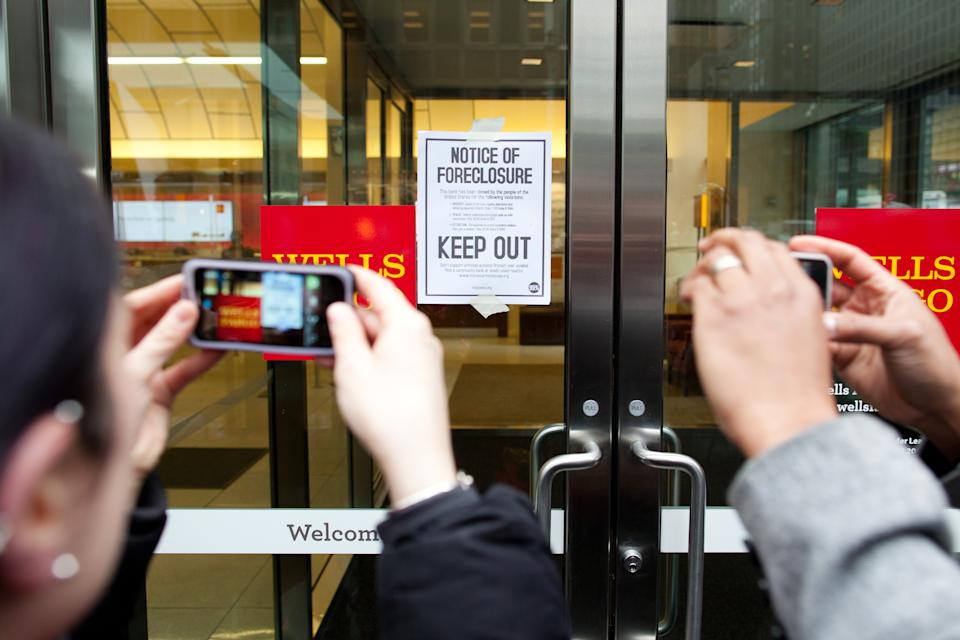 "Pedestrians photograph a flyer that reads ""Notice of Foreclosure"" taped to the doors of a Wells Fargo branch during an Occupy Wall Street march on the offices of pharmaceutical giant Pfizer, Wednesday, Feb. 29, 2012, in New York. There was a heavy police presence around the 42nd Street area as the demonstration began Wednesday morning. (AP Photo/John Minchillo)"