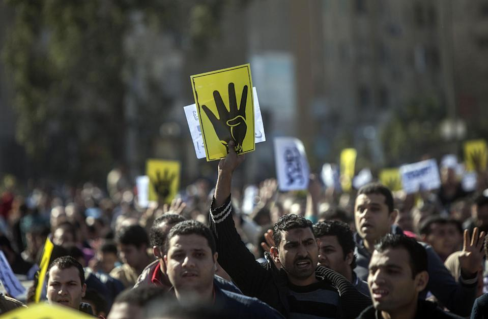 """Supporters of the Muslim Brotherhood raise four fingers, the symbol known as """"Rabaa"""", remembering those killed in the crackdown on the Rabaa al-Adawiya protest camp in Cairo last year, during a demonstration in Cairo in January 2014 (AFP Photo/Mahmoud Khaled)"""