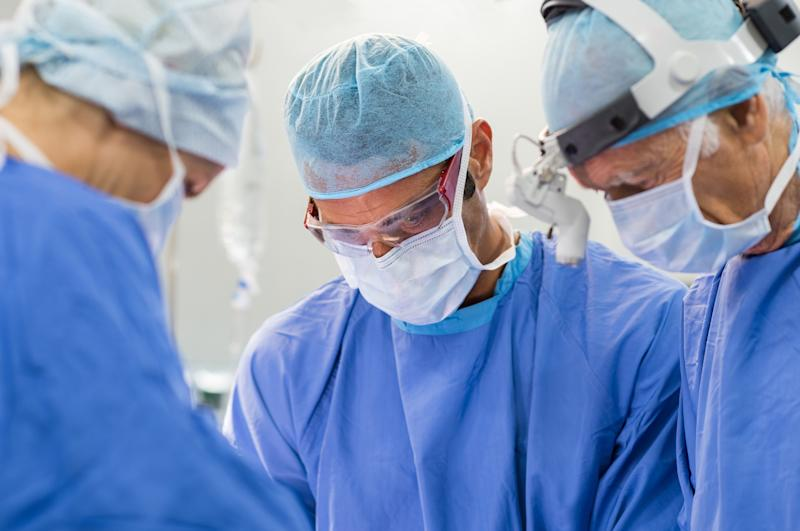 Three people in masks and blue scrubs in a circle look down, as if performing surgery.