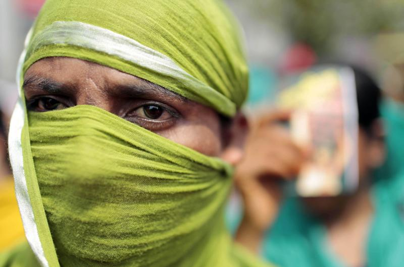 A Bangladeshi garment worker covers her face with a scarf to shelter herself from the sun as she participates in a May Day rally in Dhaka, Bangladesh, Thursday, May 1, 2014. The demonstrators demanded punishment for owners of garment factories that have had accidents in the past, compensation for victims and ensuring work place safety. (AP Photo/A.M. Ahad)