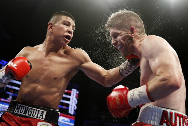 "Jaime Munguia (L) lands a hook on <a class=""link rapid-noclick-resp"" href=""/ncaaf/players/267308/"" data-ylk=""slk:Liam Smith"">Liam Smith</a> during their WBO super welterweight title fight Saturday at the Hard Rock. (John Locher/Associated Press)"