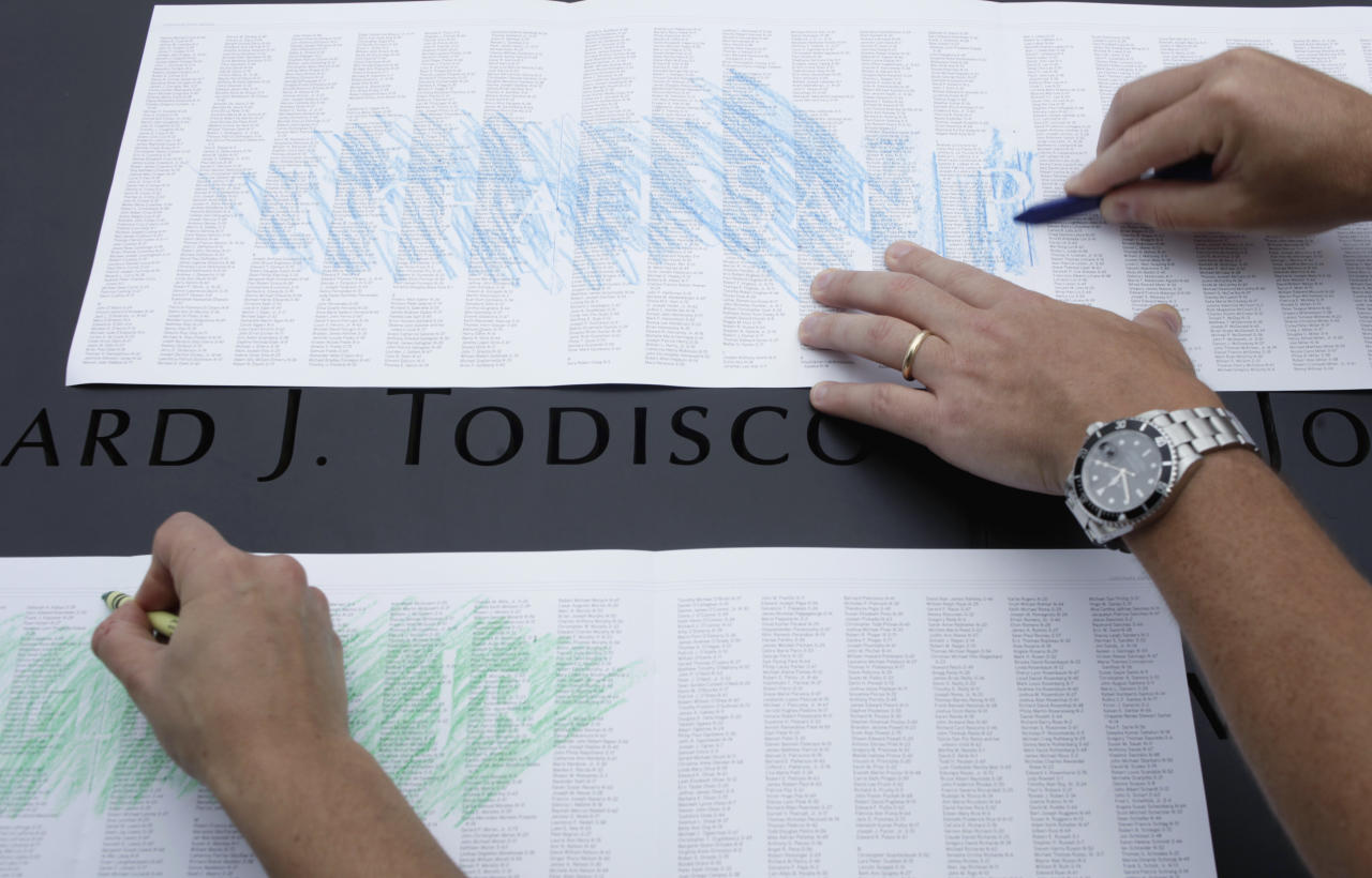 Visitors at the Sept. 11 memorial make impressions of specific names over a master list of the names of those killed in the 2001 terrorist attacks on the World Trade Center, Sunday, Sept. 11, 2011 in New York. (AP Photo/Seth Wenig, Pool)