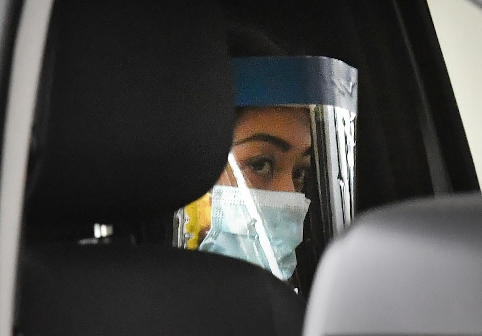 Sarah Caisip is seen wearing protective masks as she leaves the site of a funeral for her father.