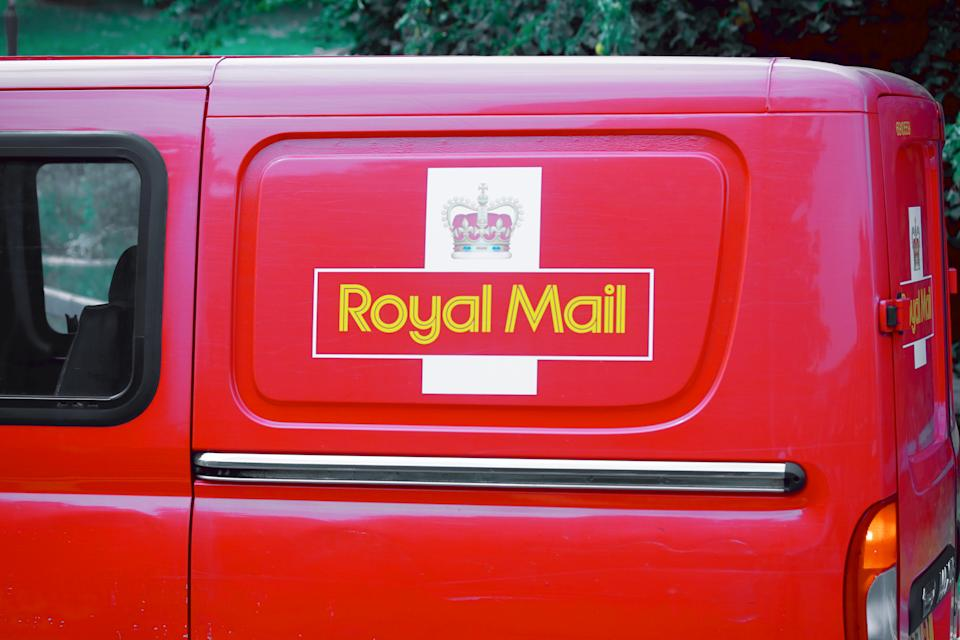 Derby, United Kingdom - July, 22th 2011: Postal delivering car of Royal Mail with logo and crown in Derby, England making a stop at traffic light. It is national postal service of the United King. Royal Mail was founded in 1516.