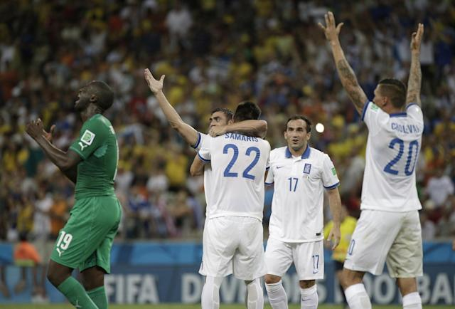 Ivory Coast's Yaya Toure reacts as Greek players celebrate after their 2-1 victory over Ivory Coast during the group C World Cup soccer match between Greece and Ivory Coast at the Arena Castelao in Fortaleza, Brazil, Tuesday, June 24, 2014. (AP Photo/Bernat Armangue)