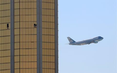 Air Force One departs Las Vegas past the broken windows on the Mandalay Bay hotel, where shooter Stephen Paddock conducted his mass shooting along the Las Vegas Strip in Las Vegas - Credit: Reuters