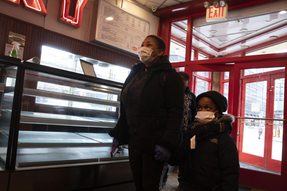 An employee of Junior's Restaurant arrives with her son to pick up a paycheck, Thursday, March 19, 2020 in the Brooklyn borough of New York. The restaurant company, which has closed its four locations due to the coronavirus, has laid off 650 of 850 employees. (AP Photo/Mark Lennihan)