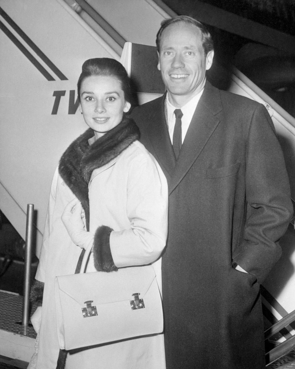 <p>The actress and her husband, Mel Ferrer, look chic as they depart New York's Idlewild Airport (now John F. Kennedy International Airport) to celebrate Christmas in Europe. </p>