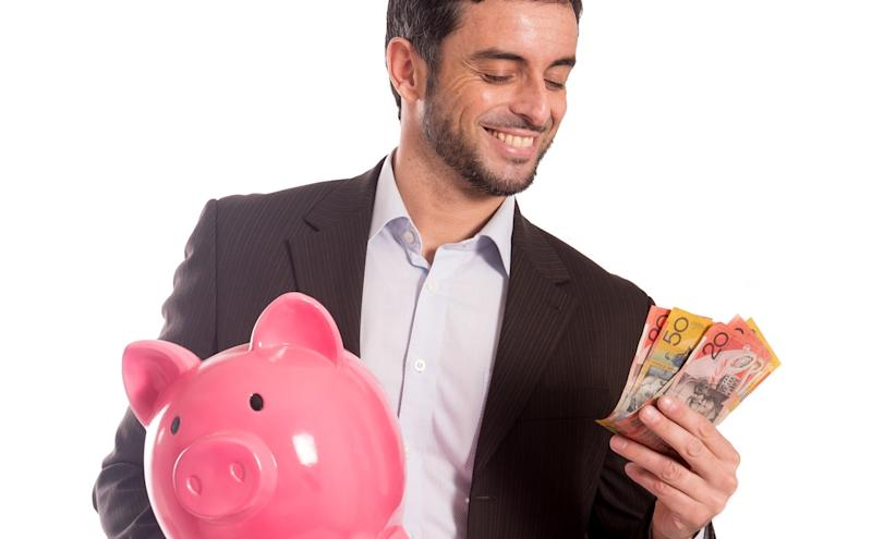 A man holding Australian banknotes smiling while holding a piggy bank in the other hand.