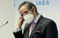 Director General of International Atomic Energy Agency, IAEA, Rafael Mariano Grossi from Argentina, removes his face mask before a news conference behind plexiglass shields after a meeting of the IAEA board of governors at the International Center in Vienna, Austria, Monday, March 1, 2021. Due to restrictions related to COVID-19, it will be organised as a virtual meeting from the IAEA. (AP Photo/Ronald Zak)