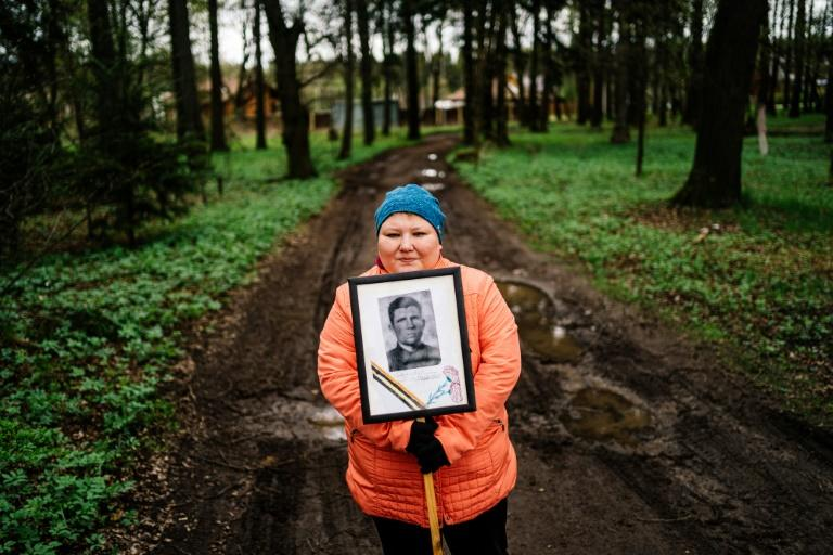 A woman carries a portrait of her grandfather near a monument in a small village outside Moscow dedicated to those who fought in World War II (AFP Photo/Dimitar DILKOFF)