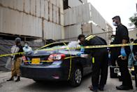 Policemen guard as members of Crime Scene Unit investigate around a car used by alleged gunmen at the main entrance of the Pakistan Stock Exchange building in Karachi on June 29, 2020. - Gunmen attacked the Pakistan Stock Exchange in Karachi on June 29, with four of the assailants killed, police said. (Photo by Asif HASSAN / AFP) (Photo by ASIF HASSAN/AFP via Getty Images)