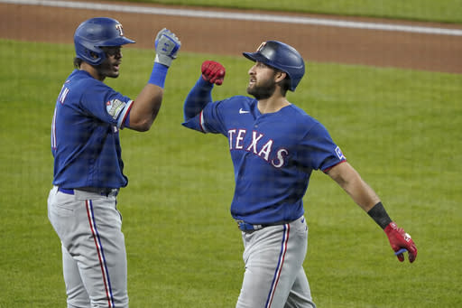 Texas Rangers' Joey Gallo, right, is greeted by Ronald Guzman, left, after hitting a solo home run against the Seattle Mariners during the second inning of a baseball game, Sunday, Sept. 6, 2020, in Seattle. (AP Photo/Ted S. Warren)