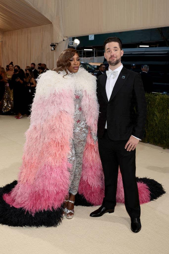 Serena Williams wears a lace glittery body suit under a floor length fuzzy three-toned cape and Alexis Ohanian wears dark suit