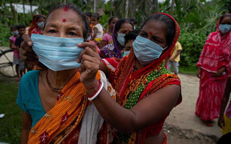 An Indian woman helps another wear a mask as a precaution against coronavirus as they stand in queue to receive free health check up at a flood affected village on the outskirts of Gauhati, India - Anupam Nath/ AP