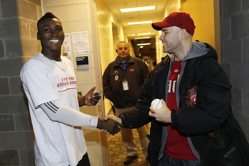 Zack Hample, right, shakes the hand of Arizona Diamondbacks' Didi Gregorius after a baseball game against the New York Yankees, Thursday, April 18, 2013, at Yankee Stadium in New York. Hample caught home run balls hit by Gregorius and Yankees' Francesco Cervelli. The Diamondbacks won 6-2 in the 12th inning. (AP Photo/John Minchillo)