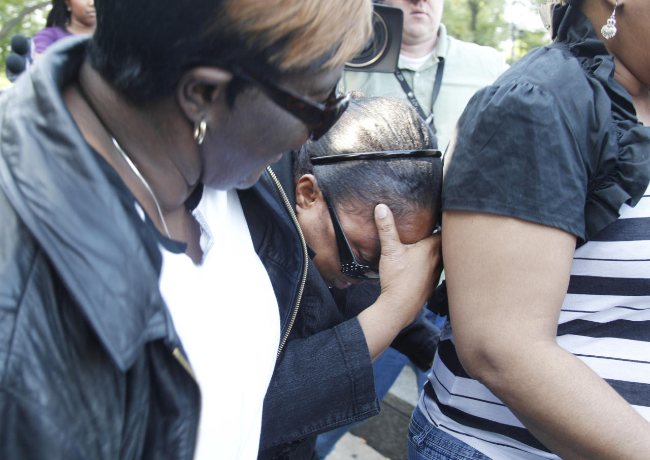Michelle Davis-Balfour, center, mother of William Balfour, speaks, hides her face Friday, May 11, 2012, in Chicago after Balfour was convicted of murdering the mother, brother and nephew of singer and actress Jennifer Hudson. Balfour faces a mandatory life prison sentence. (AP Photo/M. Spencer Green)