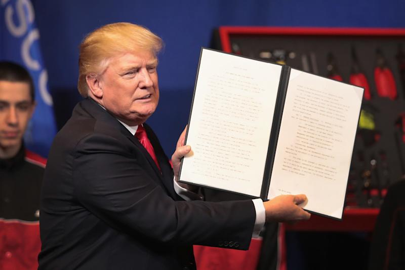 President Donald Trump signs an executive order to try to bring jobs back to American workers and revamp the H-1B visa guest worker program during a visit to the headquarters of tool manufacturer Snap-On on April 18, 2017 in Kenosha, Wisconsin. (Scott Olson via Getty Images)