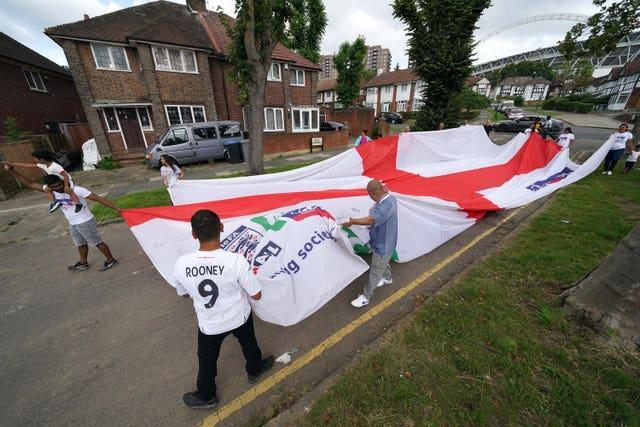 Local residents carry an official giant England Nationwide Respect campaign flag from Neeld Crescent in Brent, where Raheem Sterling grew up, to Wembley Stadium