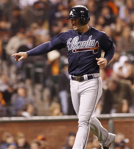 Atlanta Braves' Dan Uggla motions with his hand after scoring against the San Francisco Giants during the fifth inning of a baseball game, Thursday, May 9, 2013 in San Francisco. (AP Photo/George Nikitin)