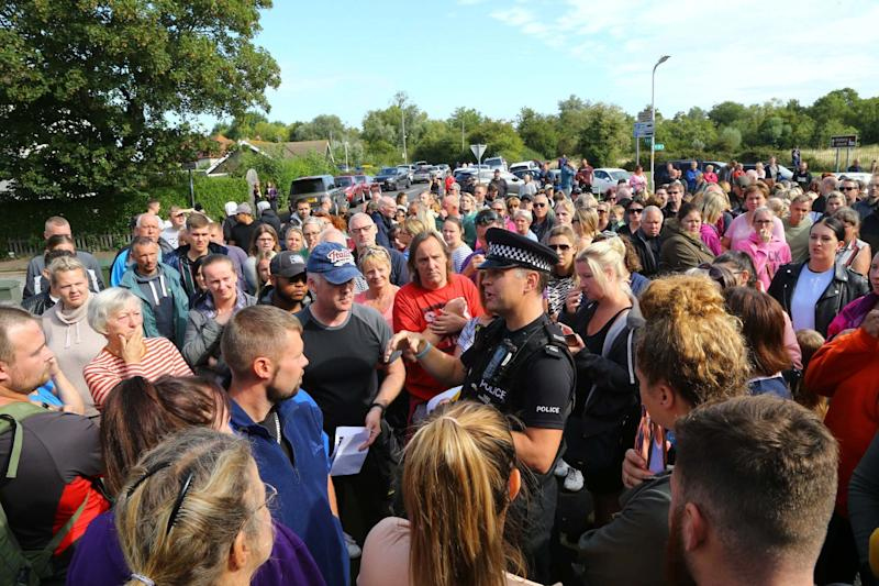 A police officer talks to members of the public gathered to join specialist search and rescue teams outside the fire station in Sandwich (PA)