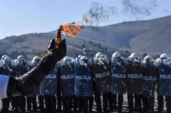A riot policeman holds a Molotov cocktail as NATO-led forces take part in a crowd and riot control exercise near the Serbian village of Vrelo on November 20, 2015 (AFP Photo/Armend Nimani)