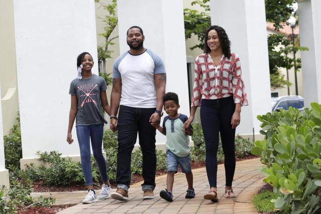 In this Tuesday, June 16, 2020 photo, D.J. Boldin, second from left, walks outside of their home with his children Madison, 10, left, and Dallas, 4, second from right, and his fiancee Sasha Jones in Miramar, Fla. Boldin is the football coach at Pahokee High School, a predominantly black school located alongside Lake Okeechobee in Florida. Recent events have given Boldin an opportunity to use his position to prepare his players for the challenges they will face when they leave the bubble that is their small town. (AP Photo/Lynne Sladky)
