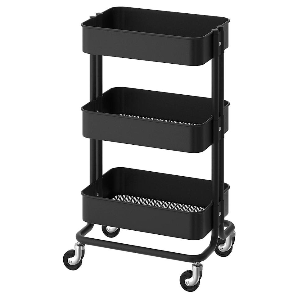 """If you prefer working mobile, trolleys are great storage units. Ivey, a fan of this IKEA Raskog cart, says it's """"a great universal storage solution for almost anything including office supplies"""" and something """"you can roll next to wherever 'office' shows up in your home for the day."""" (Yes, even the couch.) This flexible three-tiered cart is decorative enough to leave on display in a corner and slim enough to put away in a closet. $30, IKEA. <a href=""""https://www.ikea.com/us/en/p/raskog-utility-cart-black-90333976/"""" rel=""""nofollow noopener"""" target=""""_blank"""" data-ylk=""""slk:Get it now!"""" class=""""link rapid-noclick-resp"""">Get it now!</a>"""