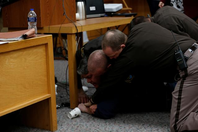 Randall Margraves (L) is tackled after he lunged at Larry Nassar (not seen) a former team USA Gymnastics doctor who pleaded guilty in November 2017 to sexual assault charges, during victim statements of his sentencing in the Eaton County Circuit Court in Charlotte, Michigan, U.S., February 2, 2018. Picture 6 of 10 in series. REUTERS/Rebecca Cook