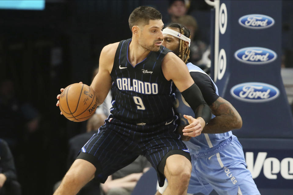 Orlando Magic's Nikola Vucevic, left, works his way around Minnesota Timberwolves' James Johnson in the second half of an NBA basketball game, Friday, March 6, 2020, in Minneapolis. (AP Photo/Jim Mone)