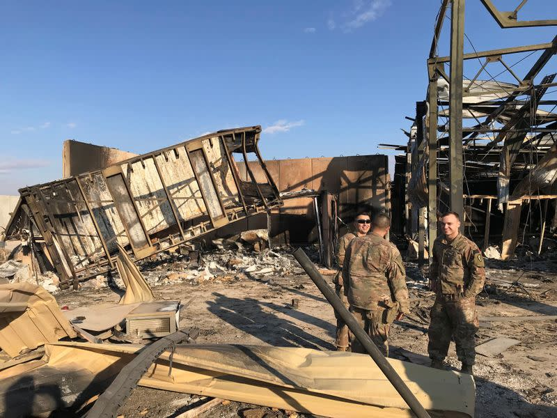 U.S. soldiers stand at the site where an Iranian missile hit at Ain al-Asad air base in Anbar province
