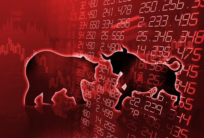 A red stock chart and screen with a bull and bear in front of it.