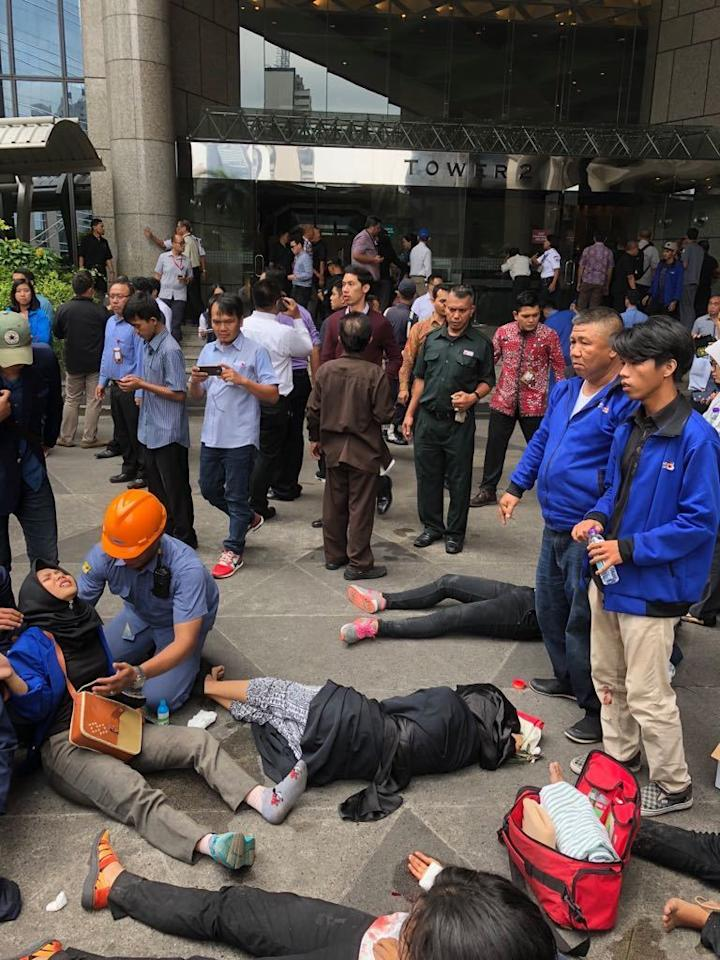<p>An Indonesian worker attends one of evacuated victims after a structure inside the Jakarta Stock Exchange tower collapsed in Jakarta, Indonesia, Jan. 15, 2018. (Photo: AP) </p>