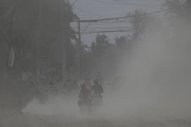 Residents on motorcycles navigate a road covered in volcanic ash at a village beside Taal volcano in Agoncillo, Batangas province, southern Philippines on Saturday Jan. 18, 2020. Local authorities have allowed some residents to return to their homes for a few hours in the morning to retrieve belongings and feed their pets or farm animals. The Taal volcano near the Philippine capital emitted more ash clouds Saturday, posing the threat of another eruption. (AP Photo/Aaron Favila)